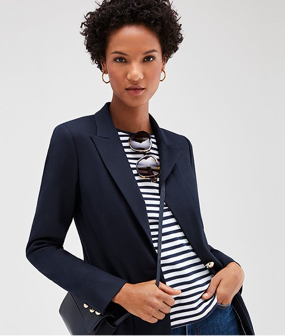 Model wears a navy blazer, striped top, jeans with a navy blue cross body bag
