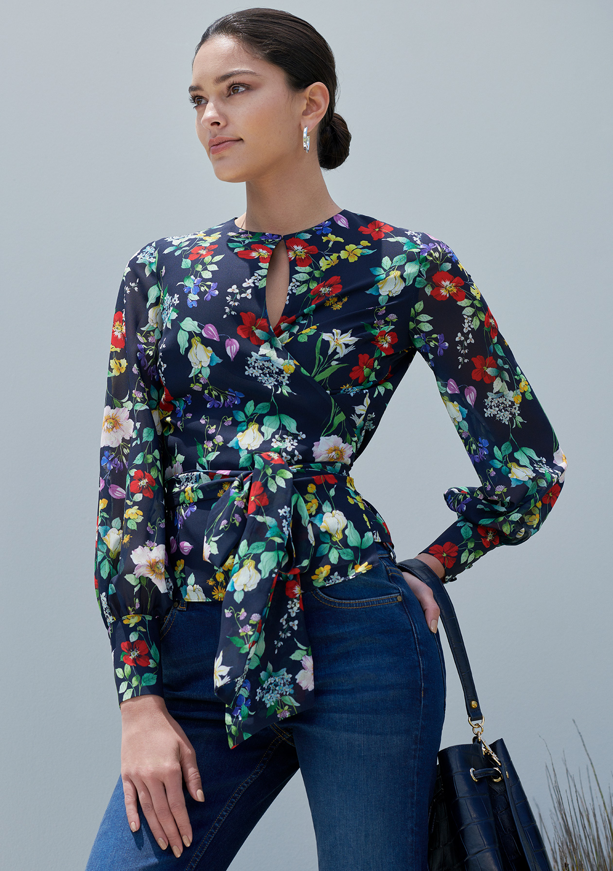 A brown haired woman poses in the Hobbs Meadow Blouse, a navy floral printed wrap top styled with denim jeans and a leather bucket bag