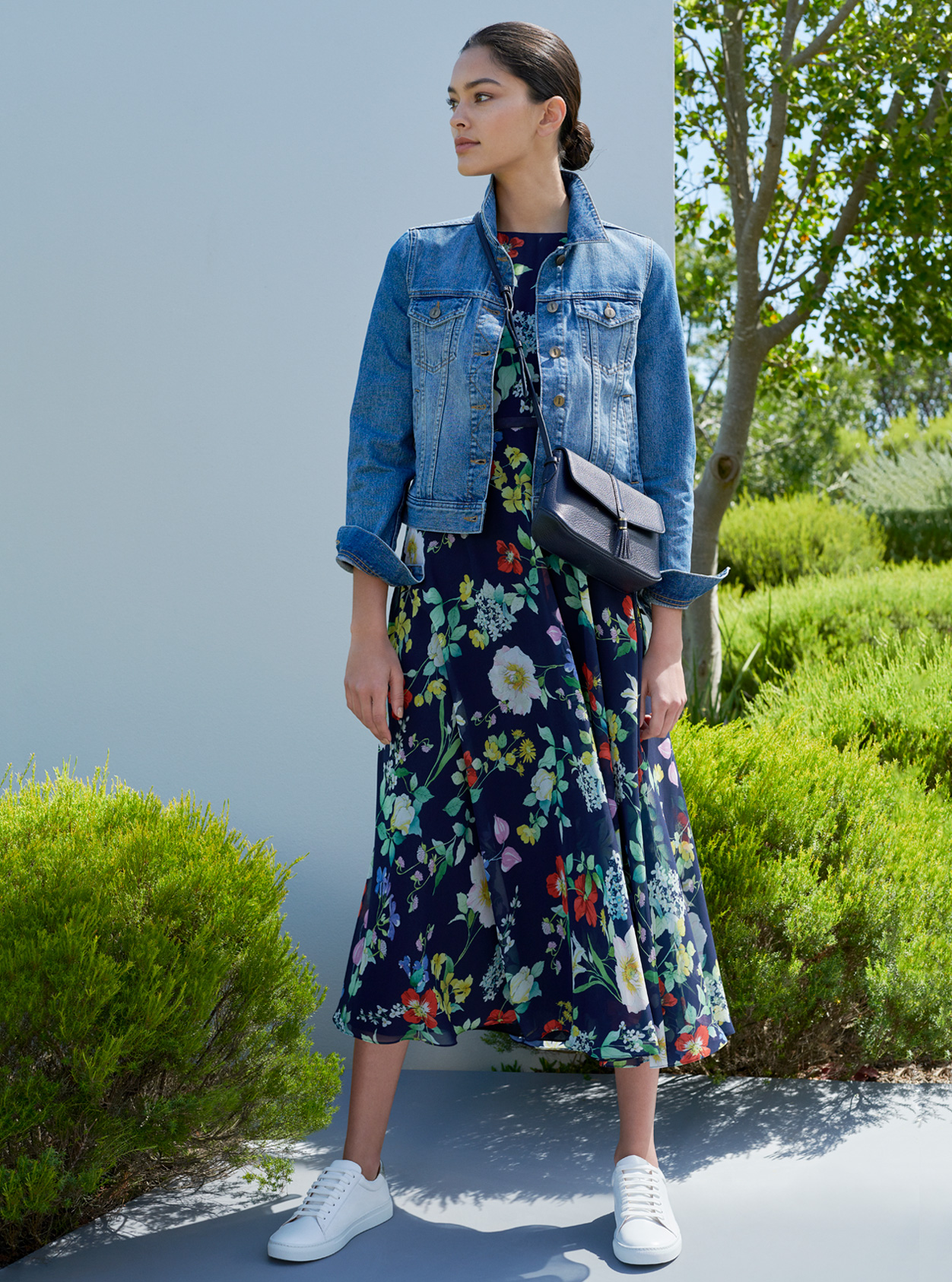 Blue denim jacket worn with a midi floral dress, white trainers and blue leather crossbody bag by Hobbs.
