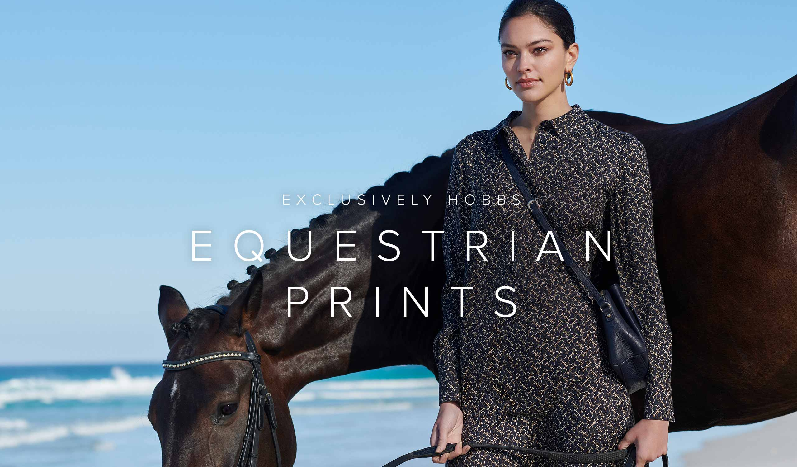 Woman poses in an  equestrian print, green and navy blue shirt dress with a black horse on a beach.
