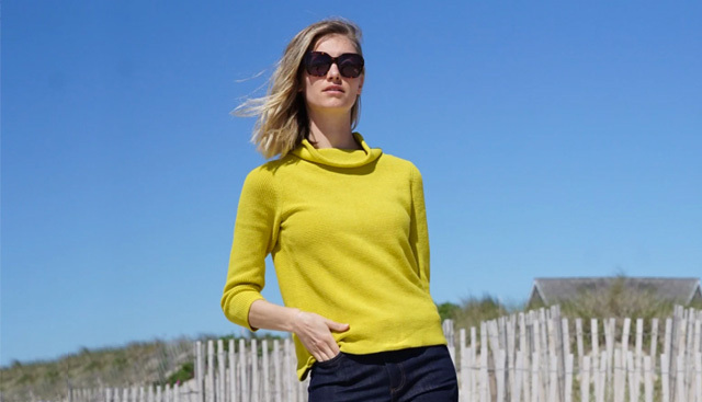 A woman poses in sunglasses, a bright yellow jumper wth dark denim jeans