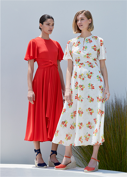 Two woman poses, one wears a flame red midi dress with sleeves and the other a white midi dress wth a red and yellow floral motif with red espadrille sandals