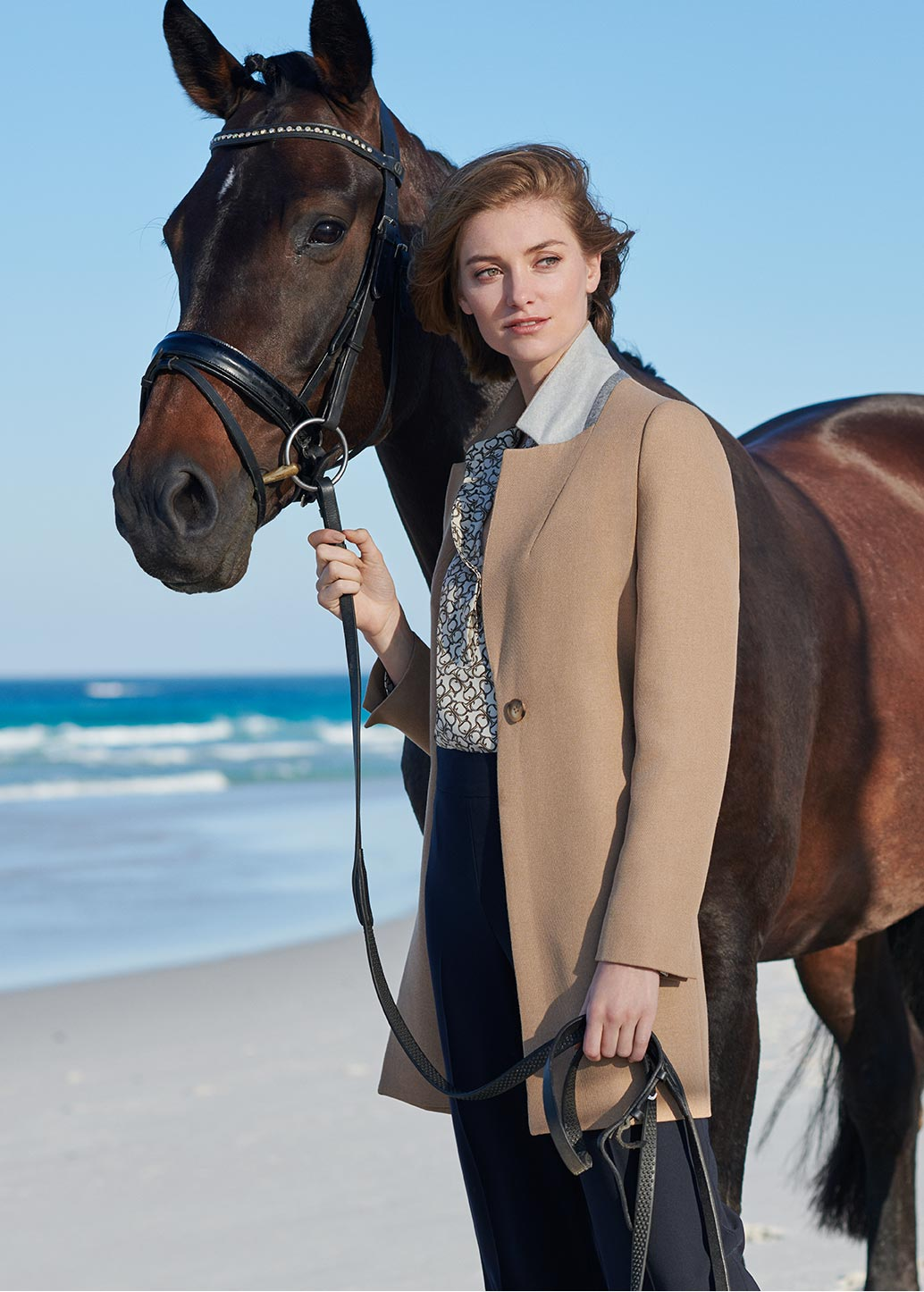Woman poses in a horse bit print navy blue and gold shirt dress with a horse in a beach