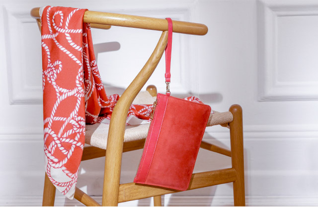 Image of a chair, casually displaying a red rope print scarf and red clutch bag