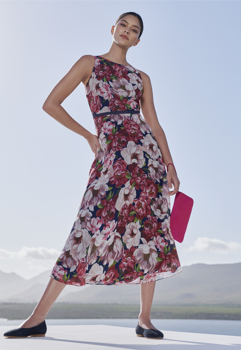 Woman poses in floral midi dress with a bright pink suede clutch bag and flat navy blue suede smart shoes.
