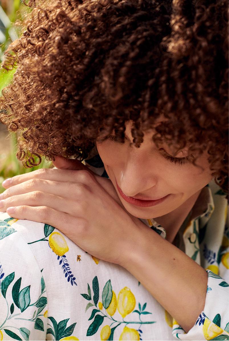 Close up of model wearing Hobbs lemon print linen shirt.