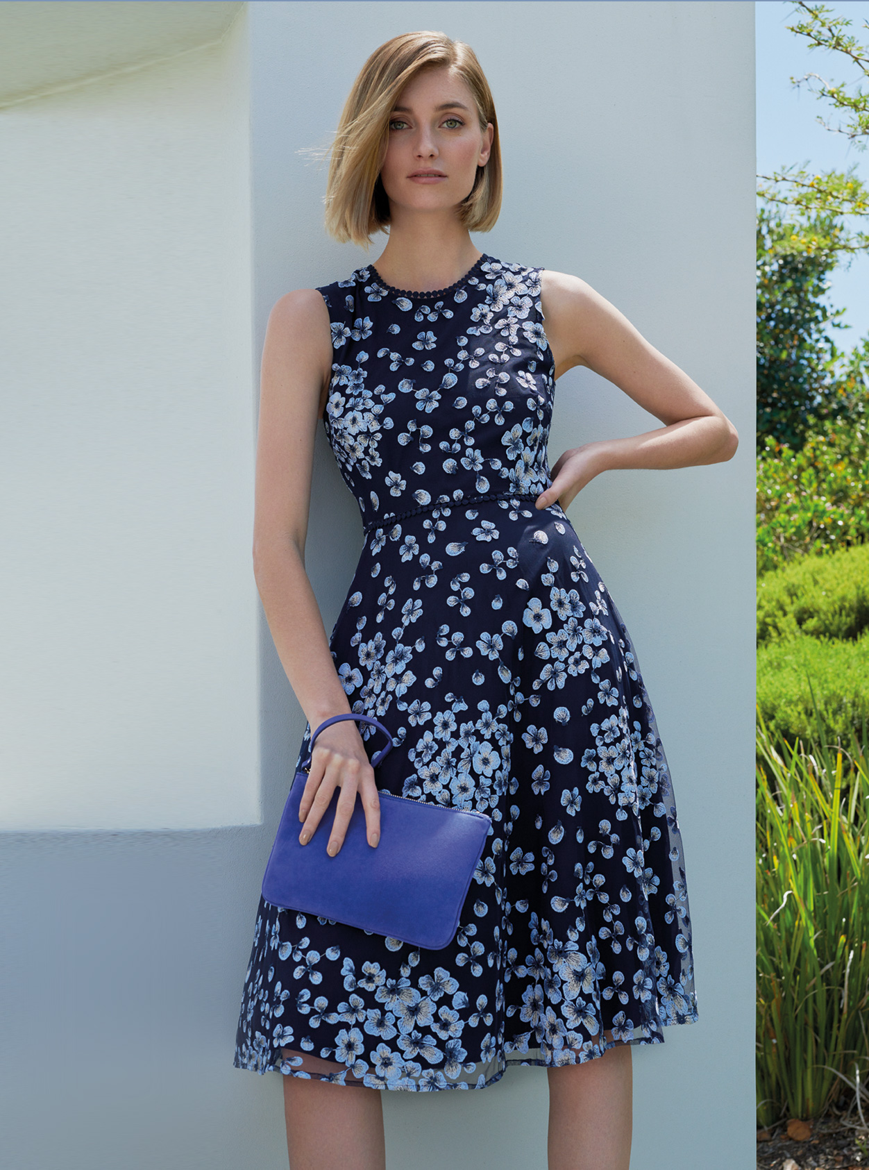 Floral fit and flare dress in blue with a matching blue wristlet clutch by Hobbs, an ideal outfit for a wedding guest.