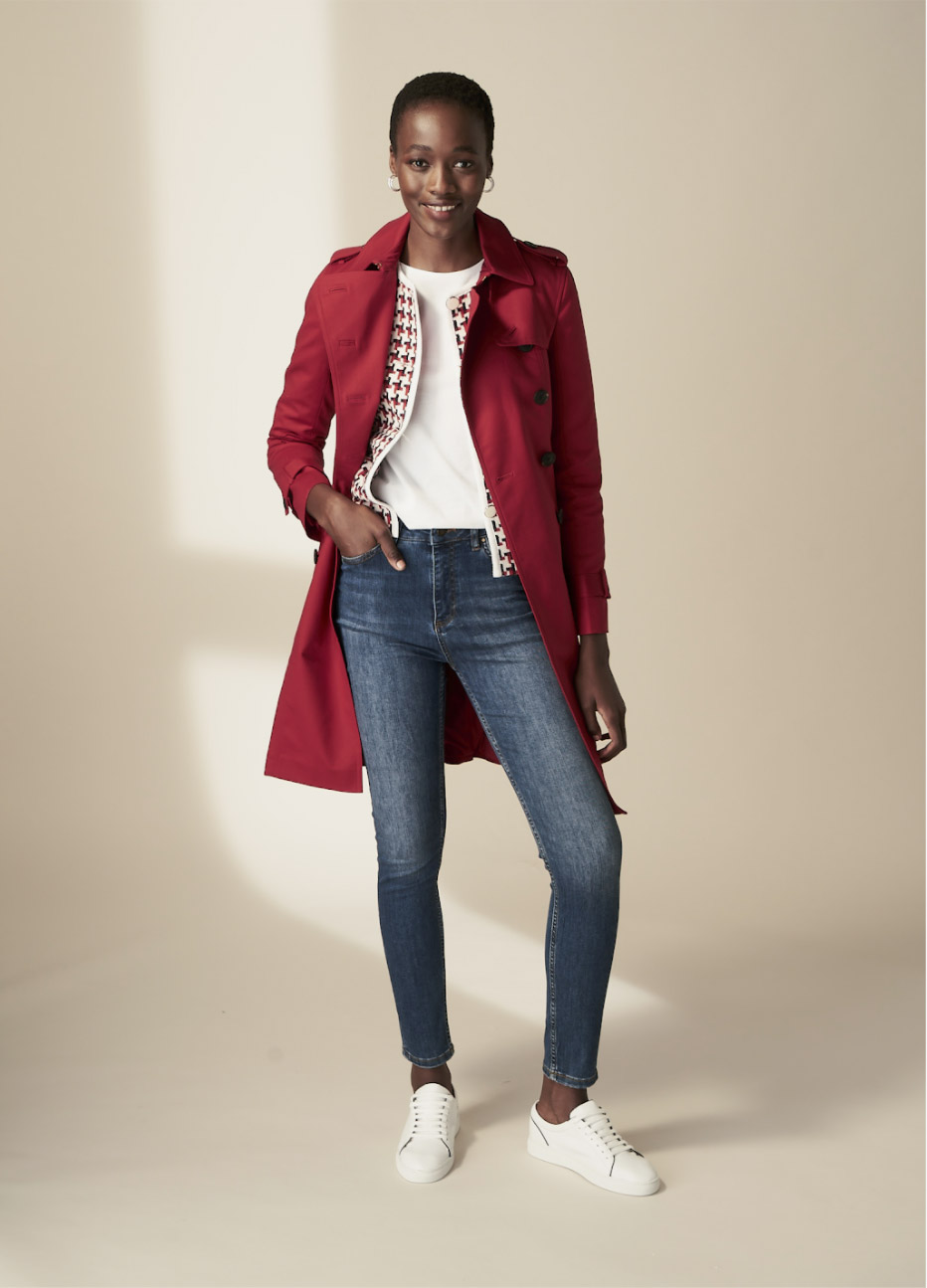 Hobbs model wearing a red trench coat over a dogtooth patterned jacket with a white t-shirt underneath, styled with blue jeans and white trainers.