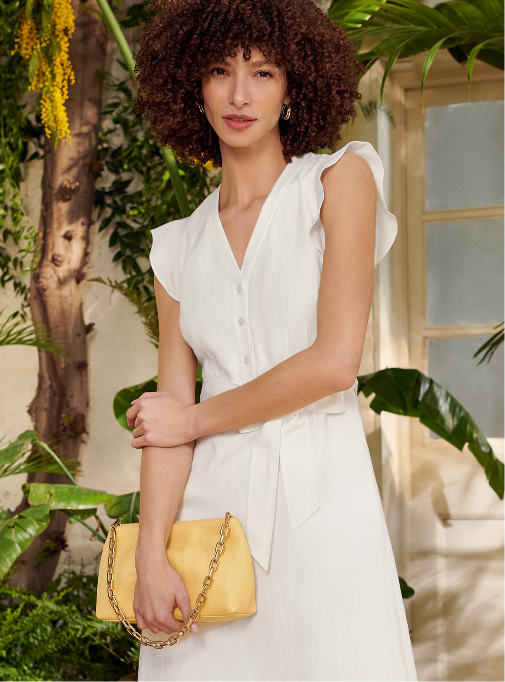 Model wearing a white dress holds a yellow clutch bag.
