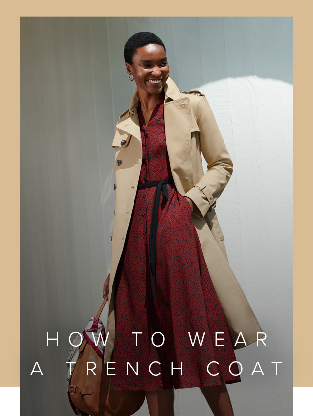 Hobbs women's trench coat in beige layered over a deep red fit and flare dress with a tie waist design, styled with a brown leather bag adorned with a silk scarf.