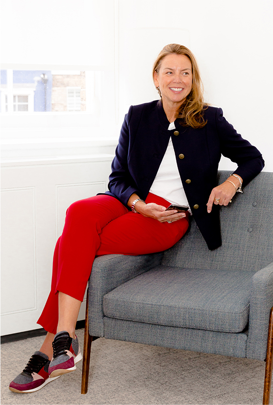 Hobbs' Product Director, Sally Ambrose, photographed sitting on a chair wearing a jacket, trousers and trainers.