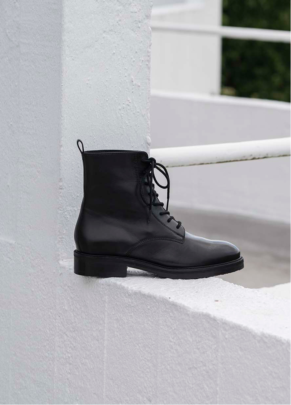 Image of a black ankle boot with buckle detail displayed on an outdoor wall.