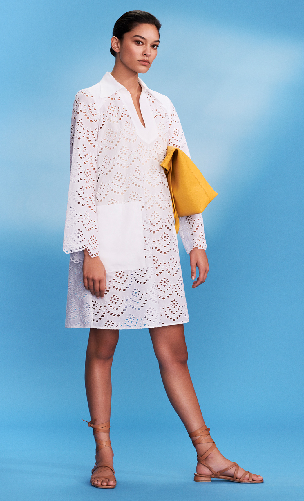 Model poses in white broaderie anglais shirt dresses styled with yellow bag and brown sandals