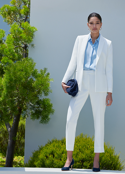 Woman stands in a white trouser suit styled with a pale blue shirt and navy suede court shoes and matching clutch bag