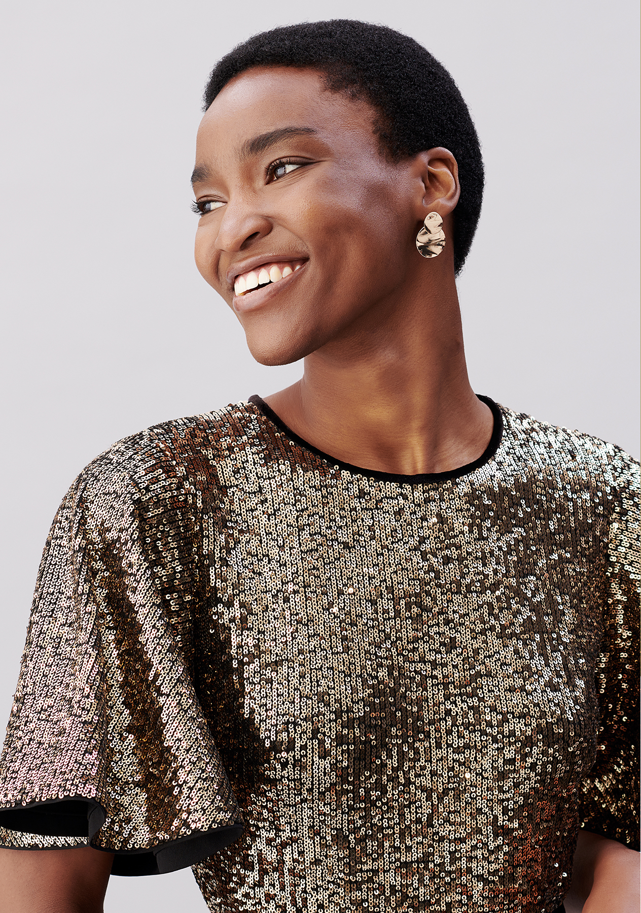 Model wears a sequin-embellished dress and earrings from Hobbs.
