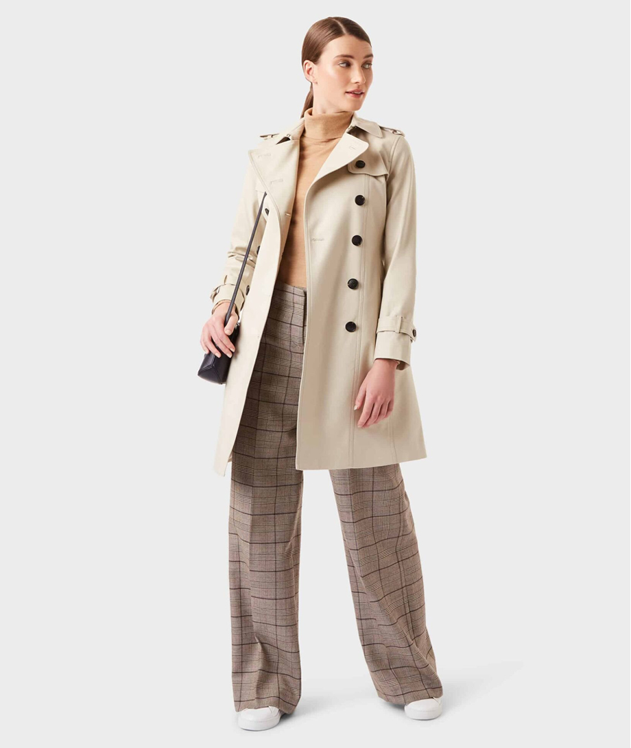 Hobbs women's trench coat in beige layered over a camel roll neck jumper with check wide trousers for women and white trainers.