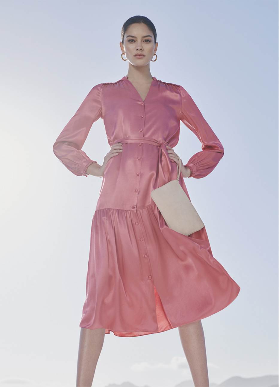 Pink satin dress with waist-tie detail for weddings and occasions, paired with matching court shoes and a wristlet clutch both in pale pink and hoop earrings, by Hobbs.