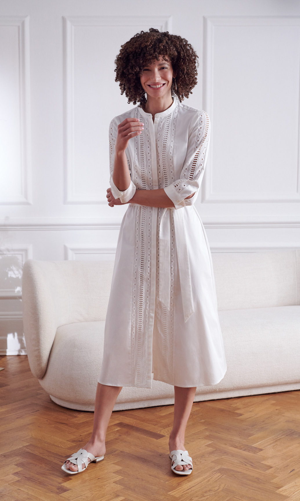 Model wearing a white cotton midi dress and leather slides stands beside a white boucle sofa.