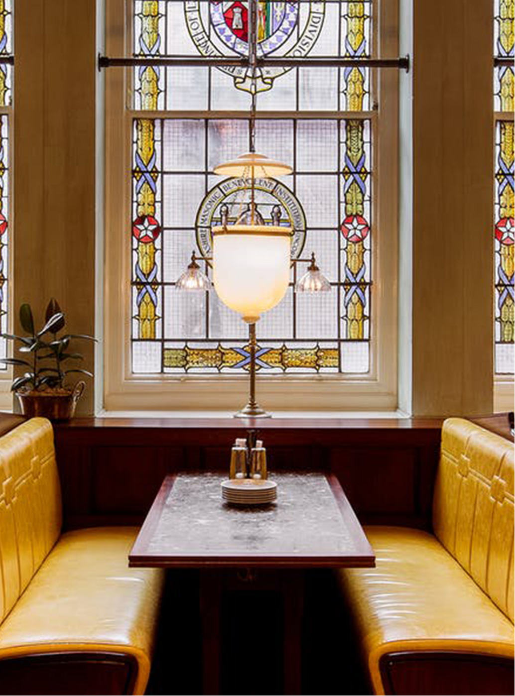The stained glass window and yellow banquette leather sofa of Dishoom in Manchester.