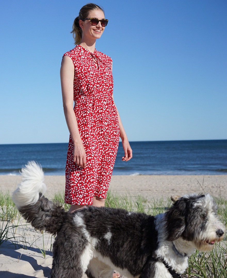Hobbs model, Irish Van Berne,photographed on the beach in a red floral sleeveless dress with a grey and white dog.