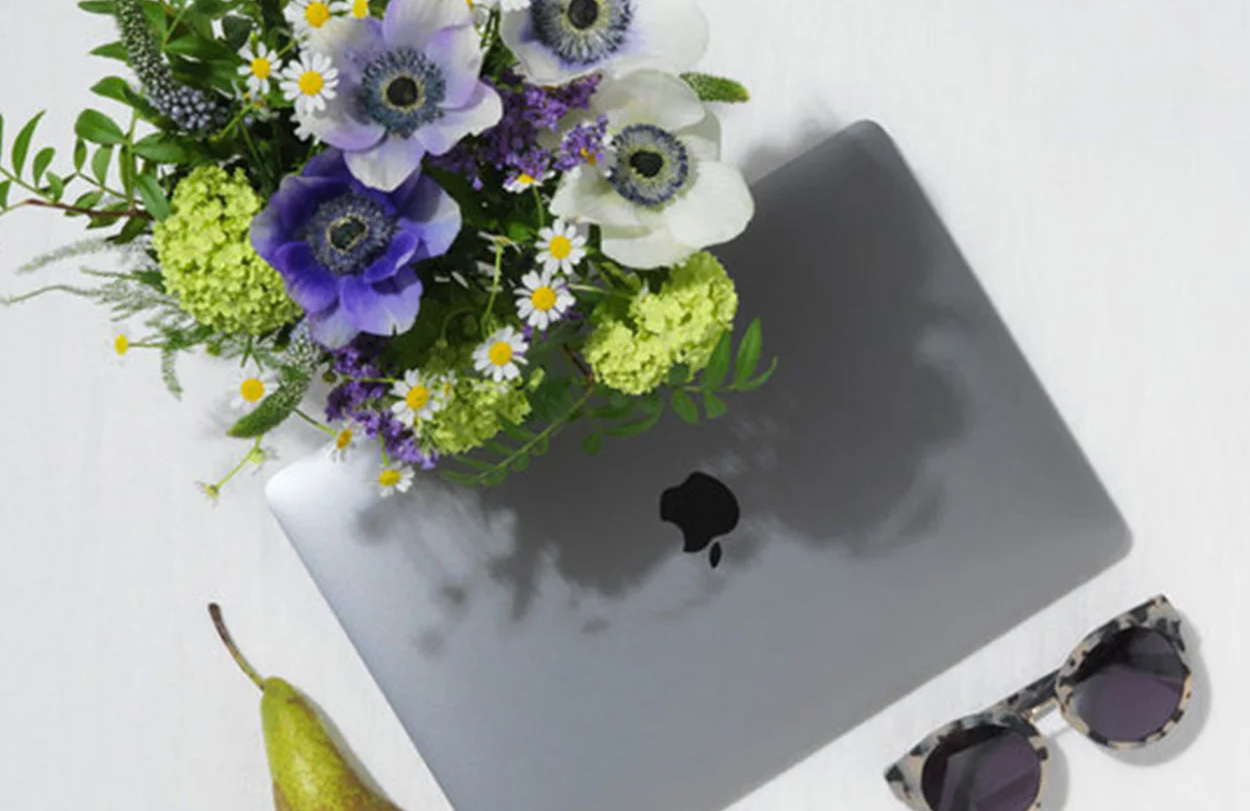 Working From Home wiith flowers, fruit and laptop