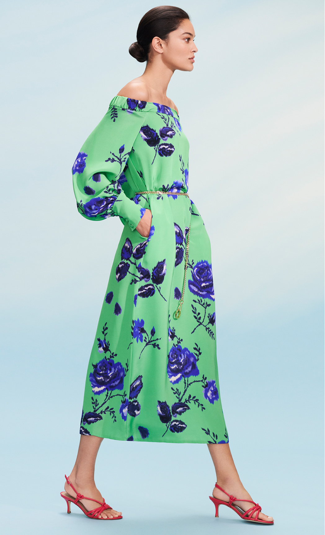 Model poses in a off the shoulder paradise green with cobalt blue floral print midi dress