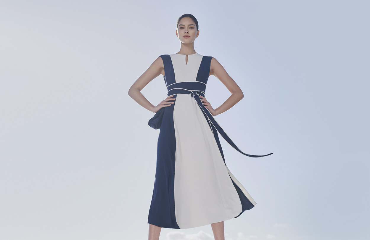Fit and flare occasion dress in white and navy with a waist tie detail paired with espadrille sandals in navy, by Hobbs.