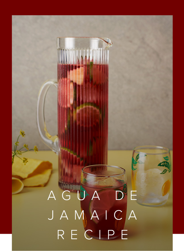 Image of jug and glasses filled with Agua De Jamaica and sliced fruit.