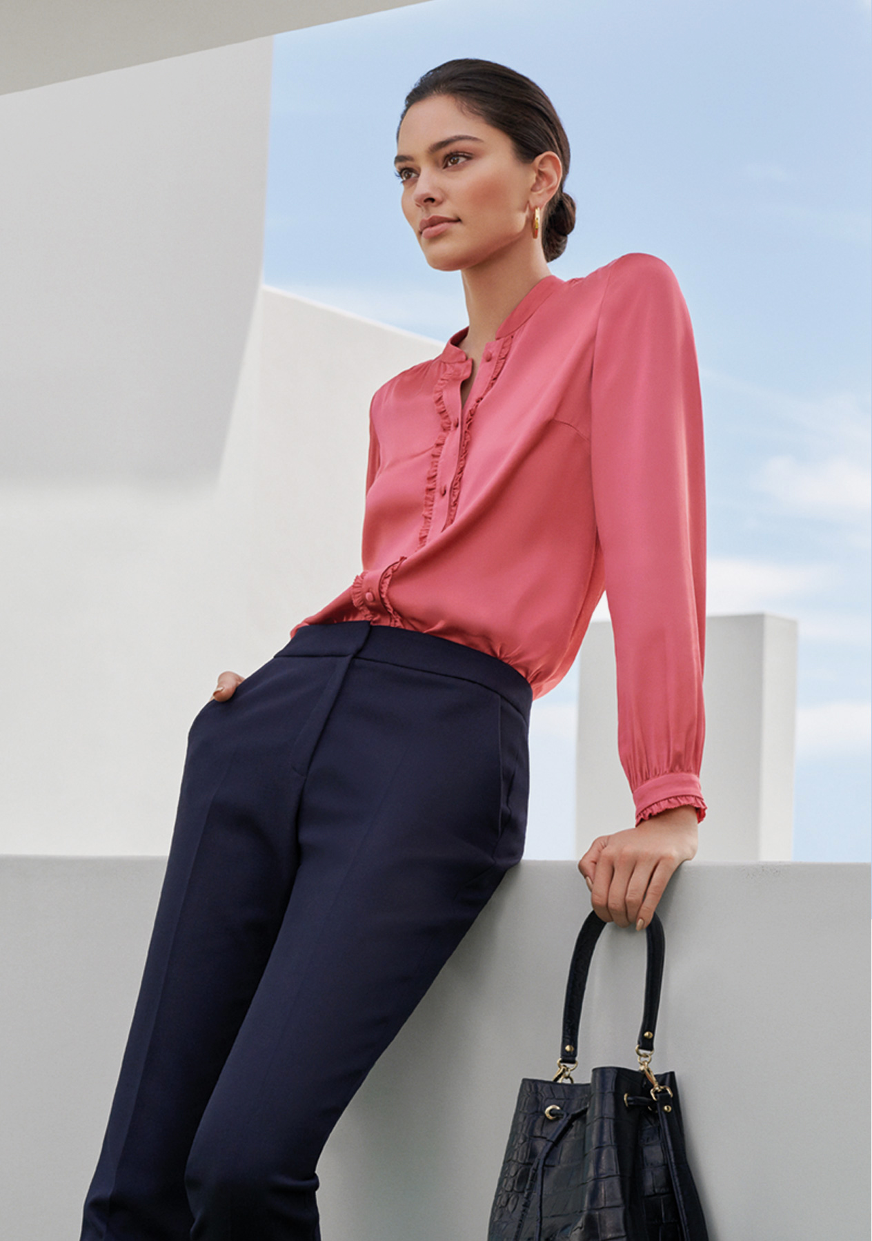 Satin shirt in pink worn with navy blue tailored trousers and a black leather bucket bag, by Hobbs.
