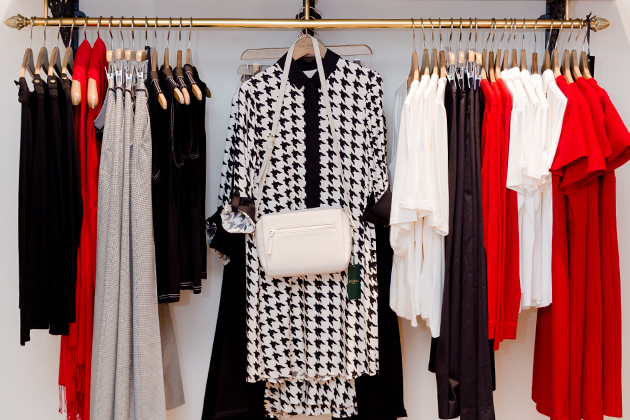 A clothing rail in a Hobbs store. The hanger in the middle shows a dogtooth patterned shirt dress in black and white with a crossbody leather bag in white. The hangers on either sides feature garments in black, white, grey and red.