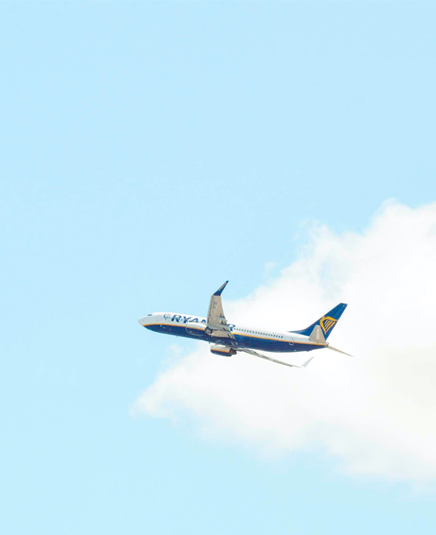 An aeroplane flys across a blue sky with a cloud