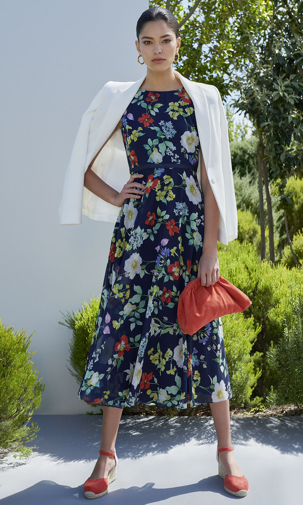 Woman poses in dark blue floral midi dress styles with a white blazer, bright orange red suede pounch clucth bag with matching espadrille sandals.