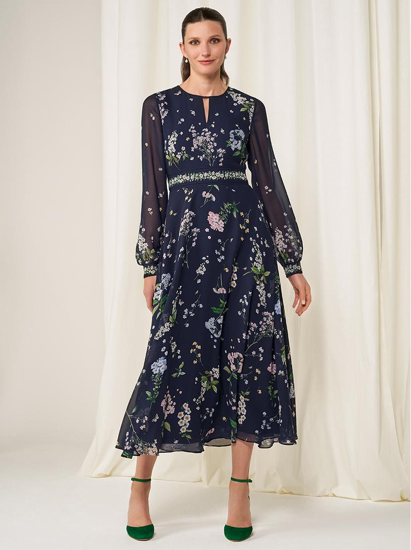 Model wears a floral silk midi dress with heels.