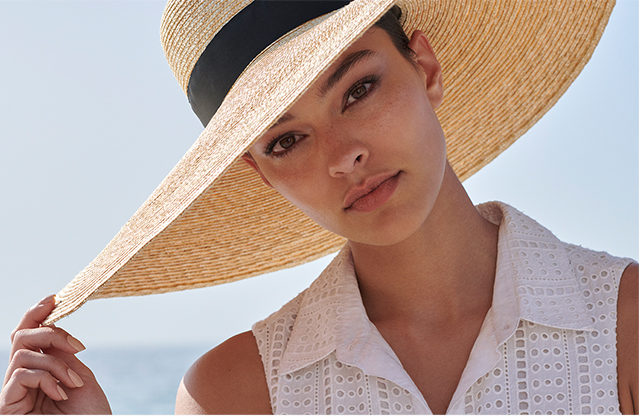 Dark haired woman wears a wide brimmed straw hat with a black band and wears a white broderie anglais sleeveless shirt