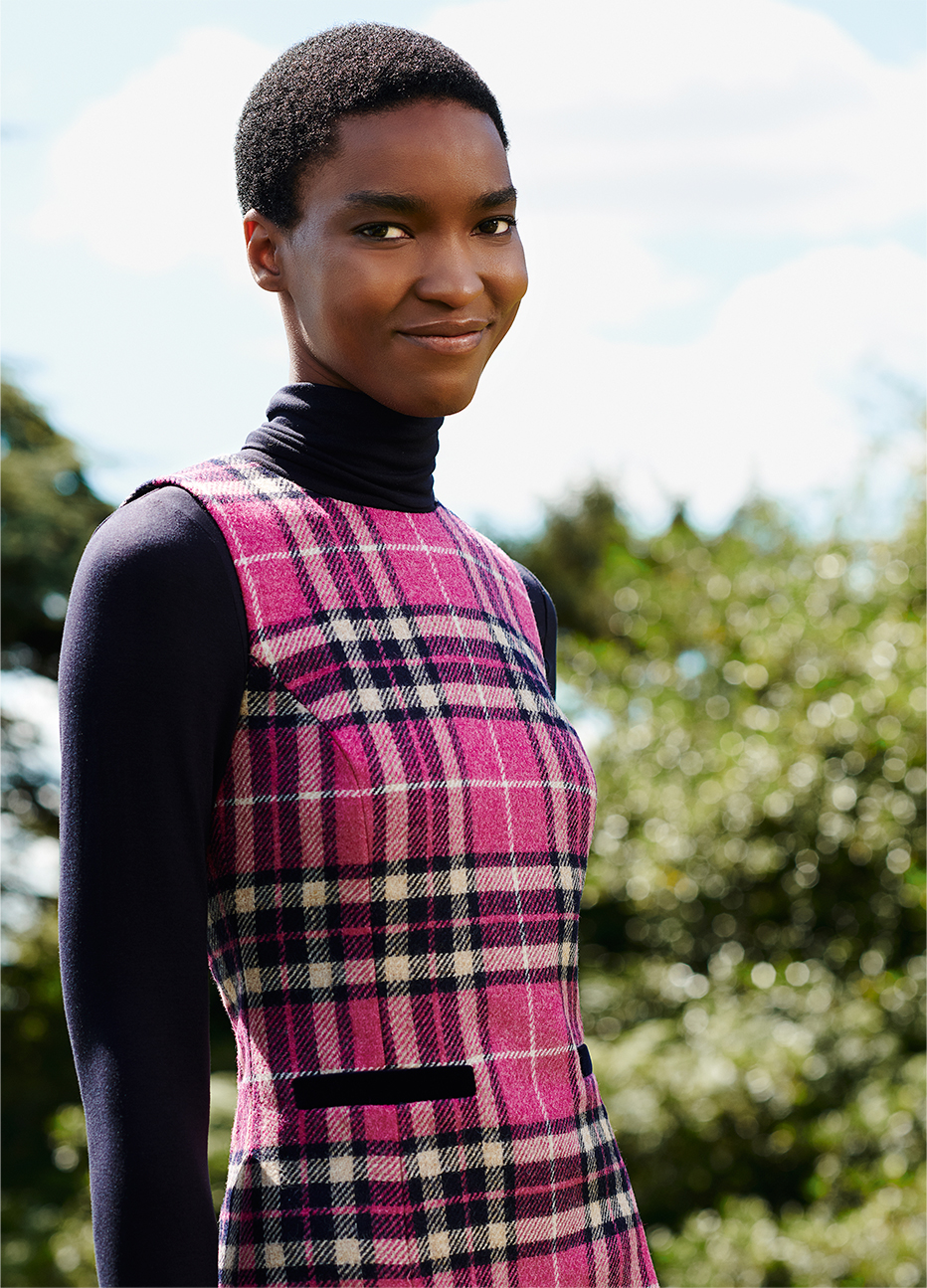 Close-up image of model wearing a checked tunic dress over a roll neck top.