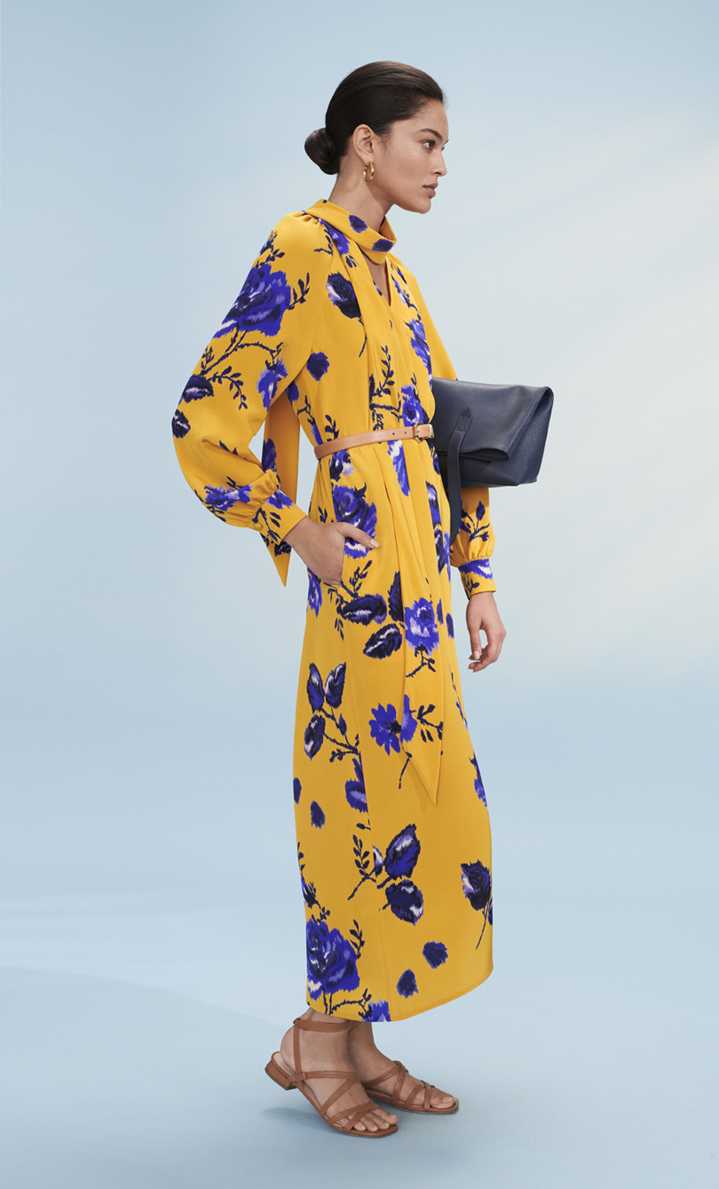 Model poses in a sunflower yellow dress with cobalt flower print with a blue clutch bag.