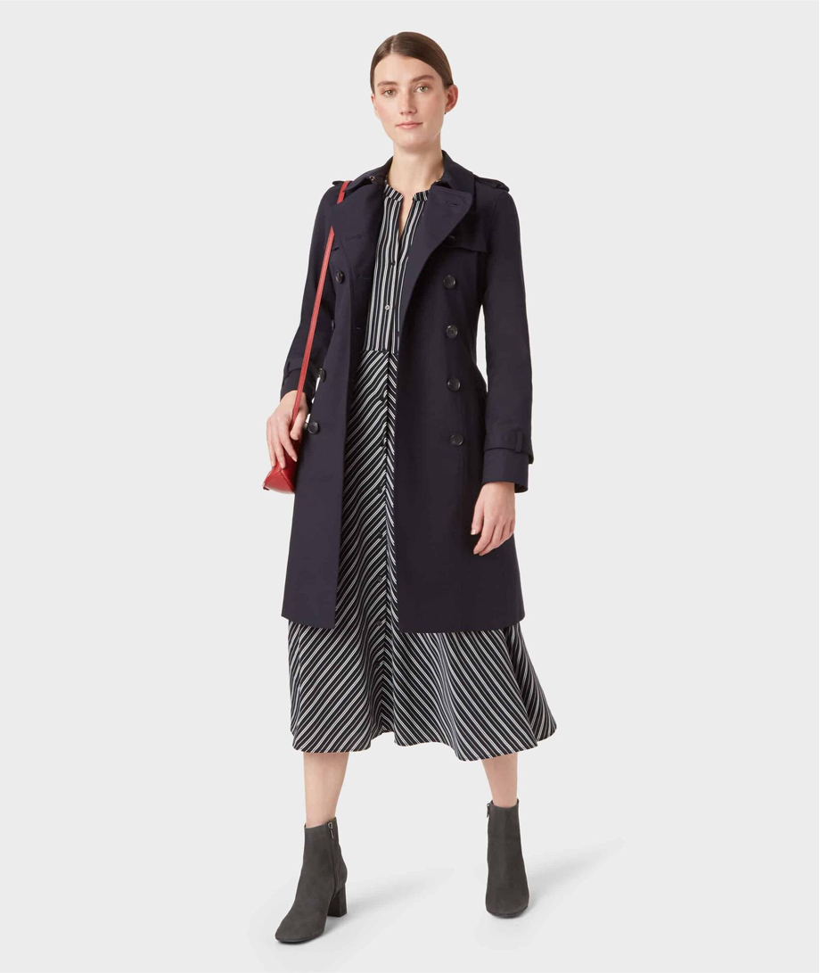 Hobbs women's trench coat in black layered over a black shirt dress styled with black leather ankle boots and a red leather crossbody bag.