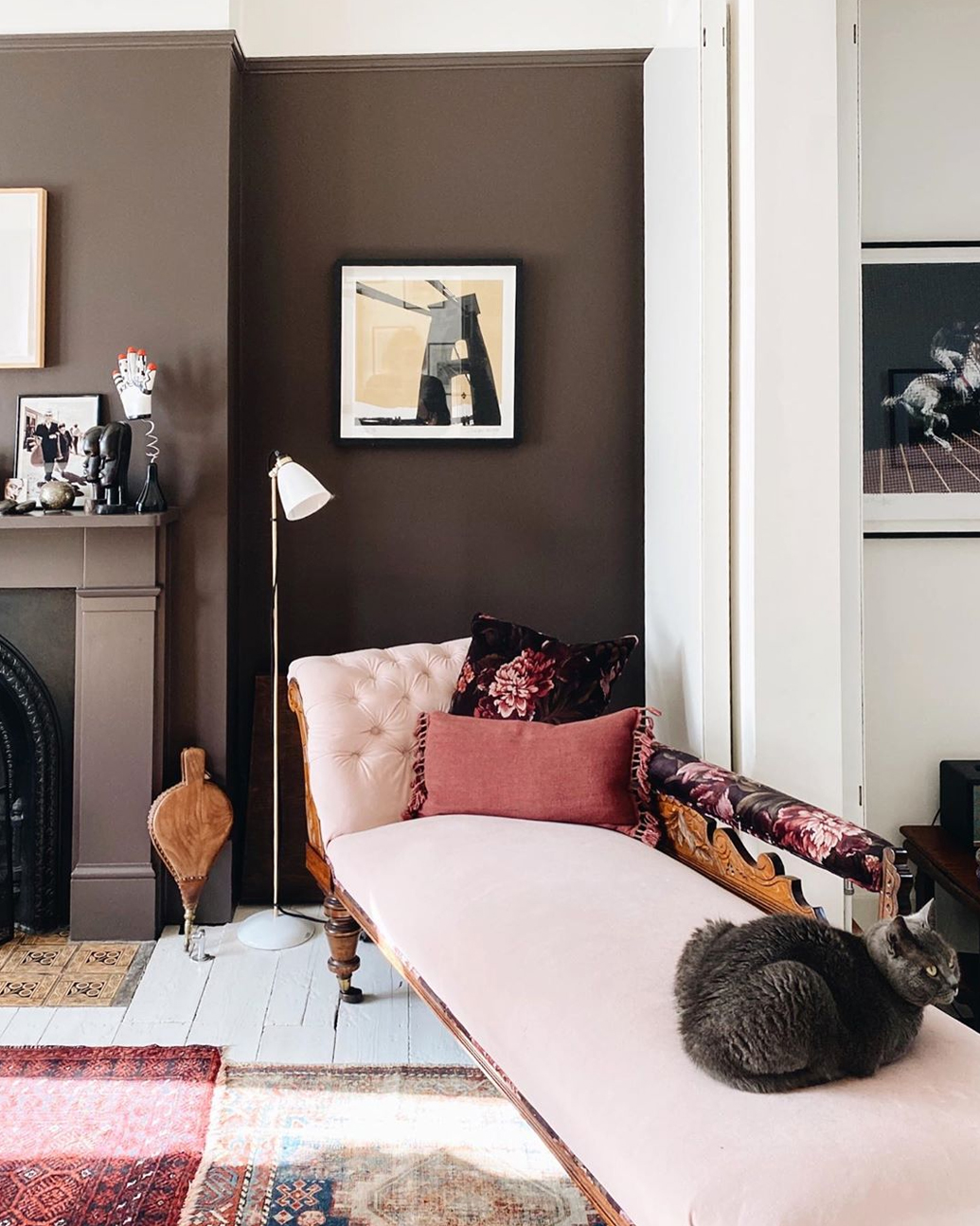 Interior shot from @madaboutthehouse featuring dark moody walls and pink soft furnishings..