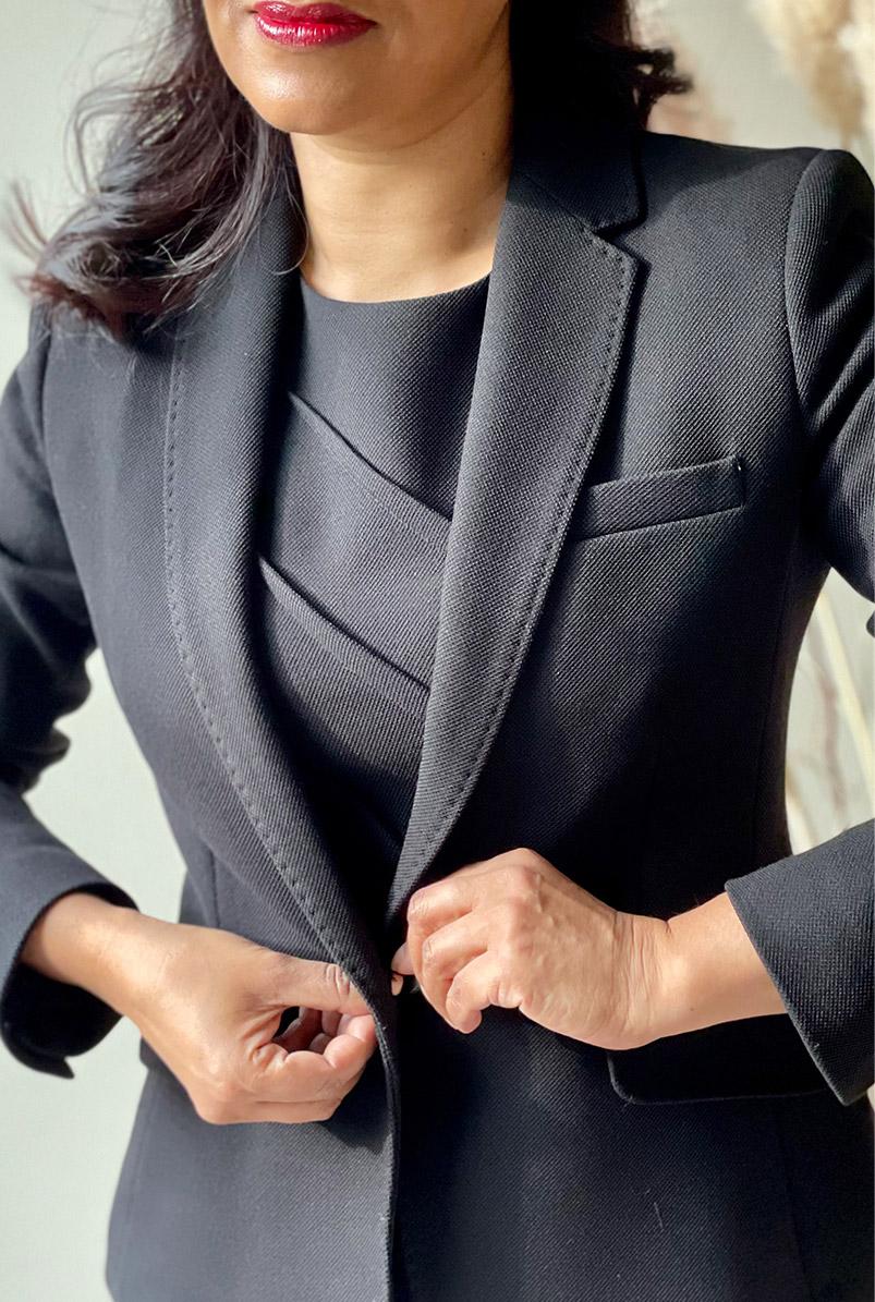 Close-up of fashion blogger Monika Mandal fastening Hobbs petite Ophelia black jacket.