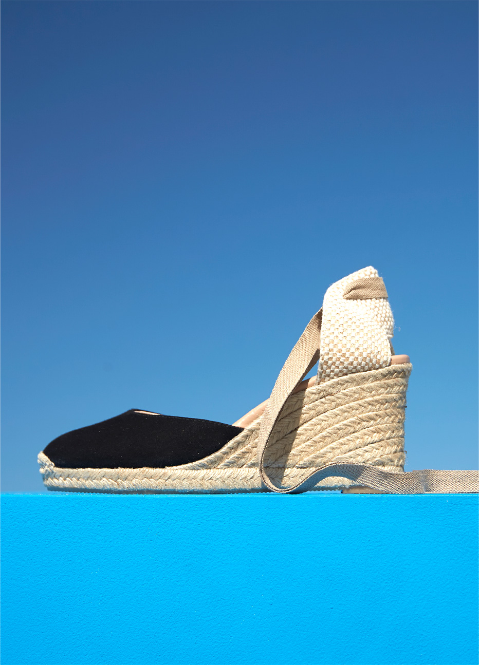 Black espadrille wedge with an ankle wrap design by Hobbs set against a blue background.
