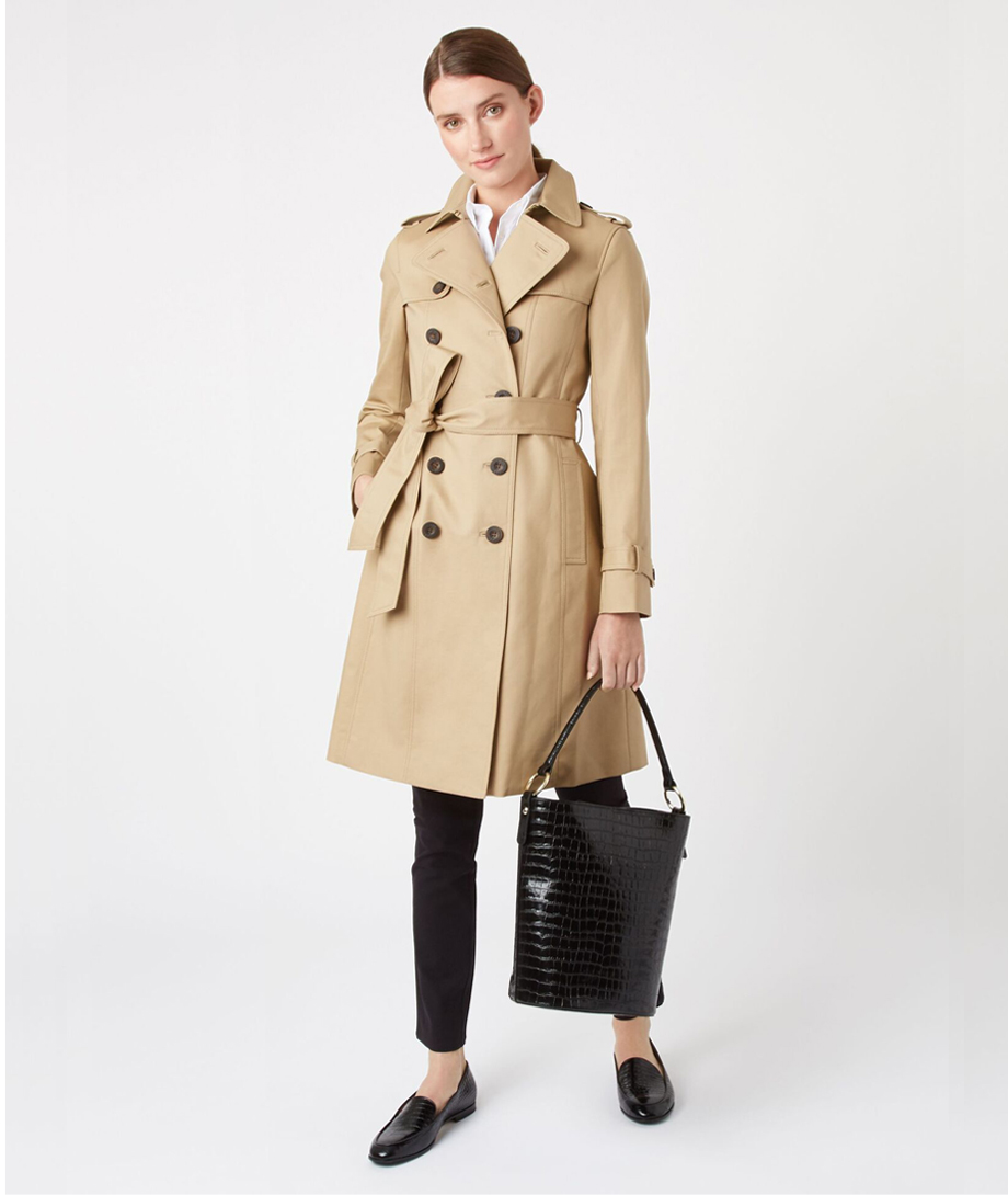 Hobbs women's trench coat in beige worn with black slim fit trousers, black leather loafers and a black leather bucket bag.