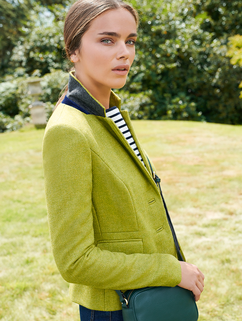 Hobbs contemporary women's blazer made with wool in green layered over a striped top, a green crossbody bag and blue jeans.