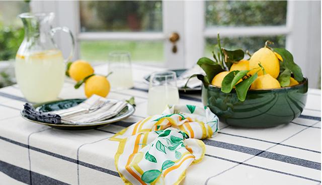 Kitchen worktop displayed with a jug of lemonade, a bowl of lemons and Hobbs lemon print scarf.