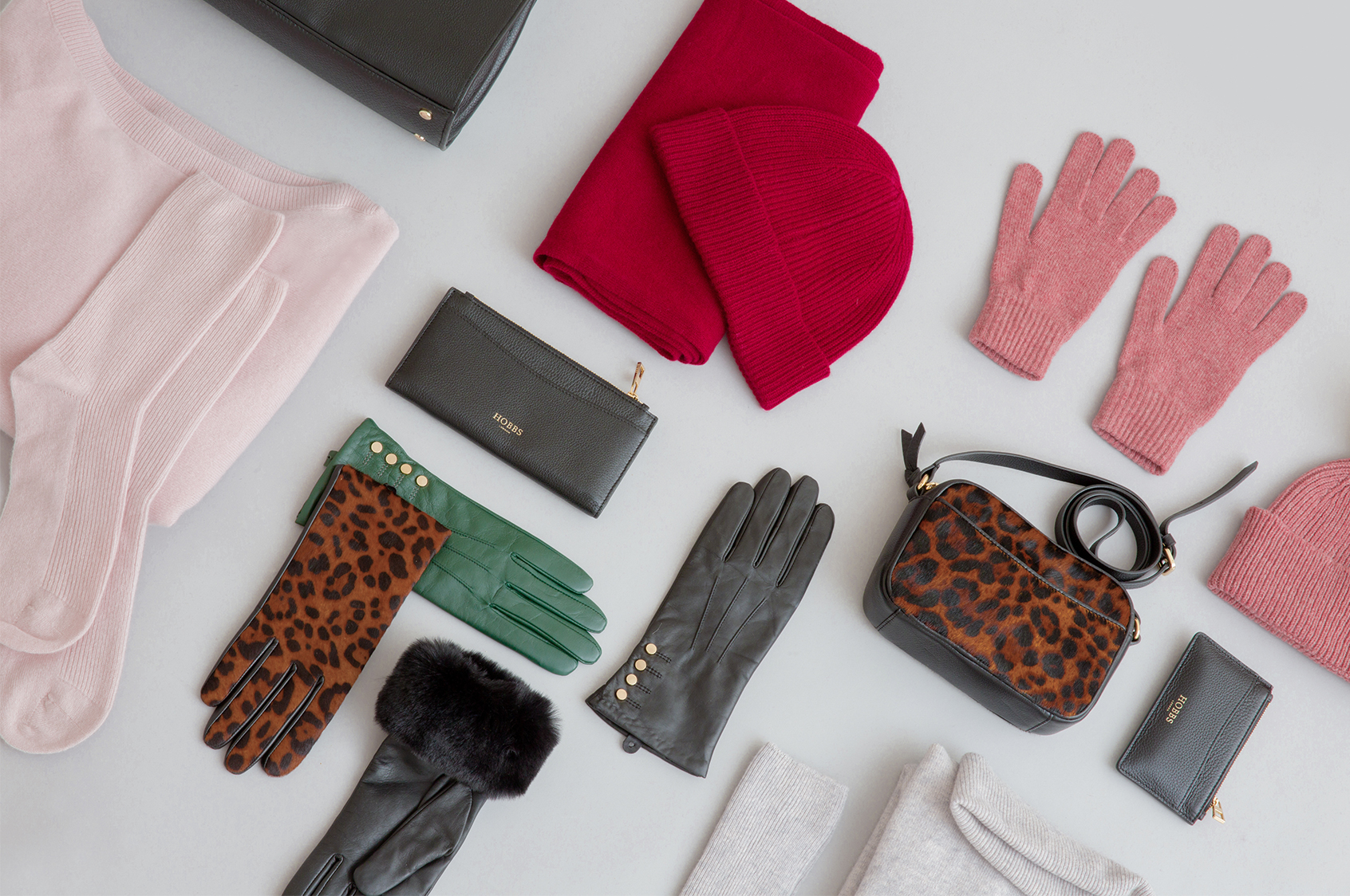 A selection of Christmas gifts including leather accessories and knitted hats, gloves and scarves.
