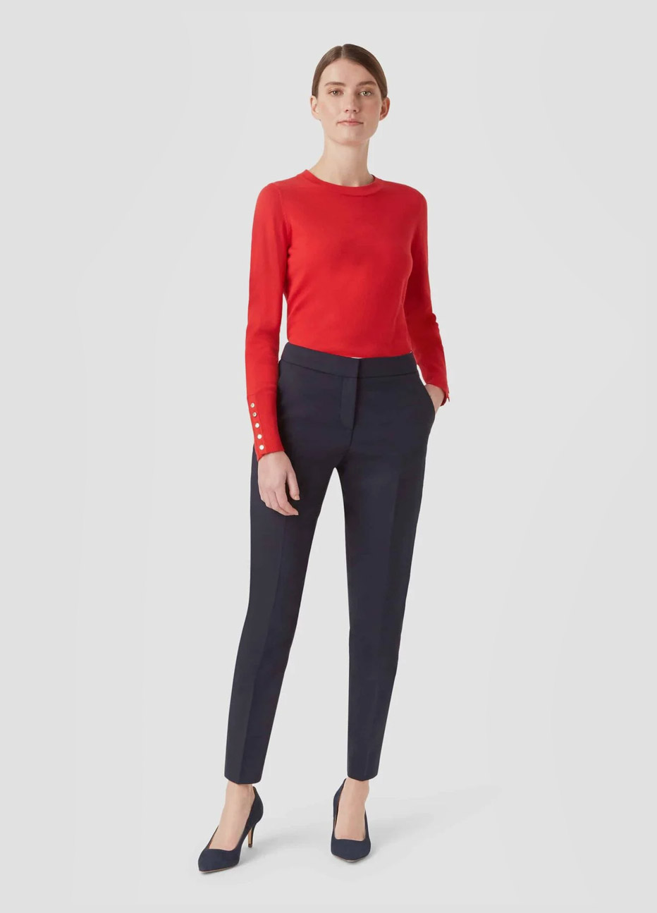 Red knitted jumper with buttons on sleeves paired with black slim fit trousers and black court shoes by Hobbs.