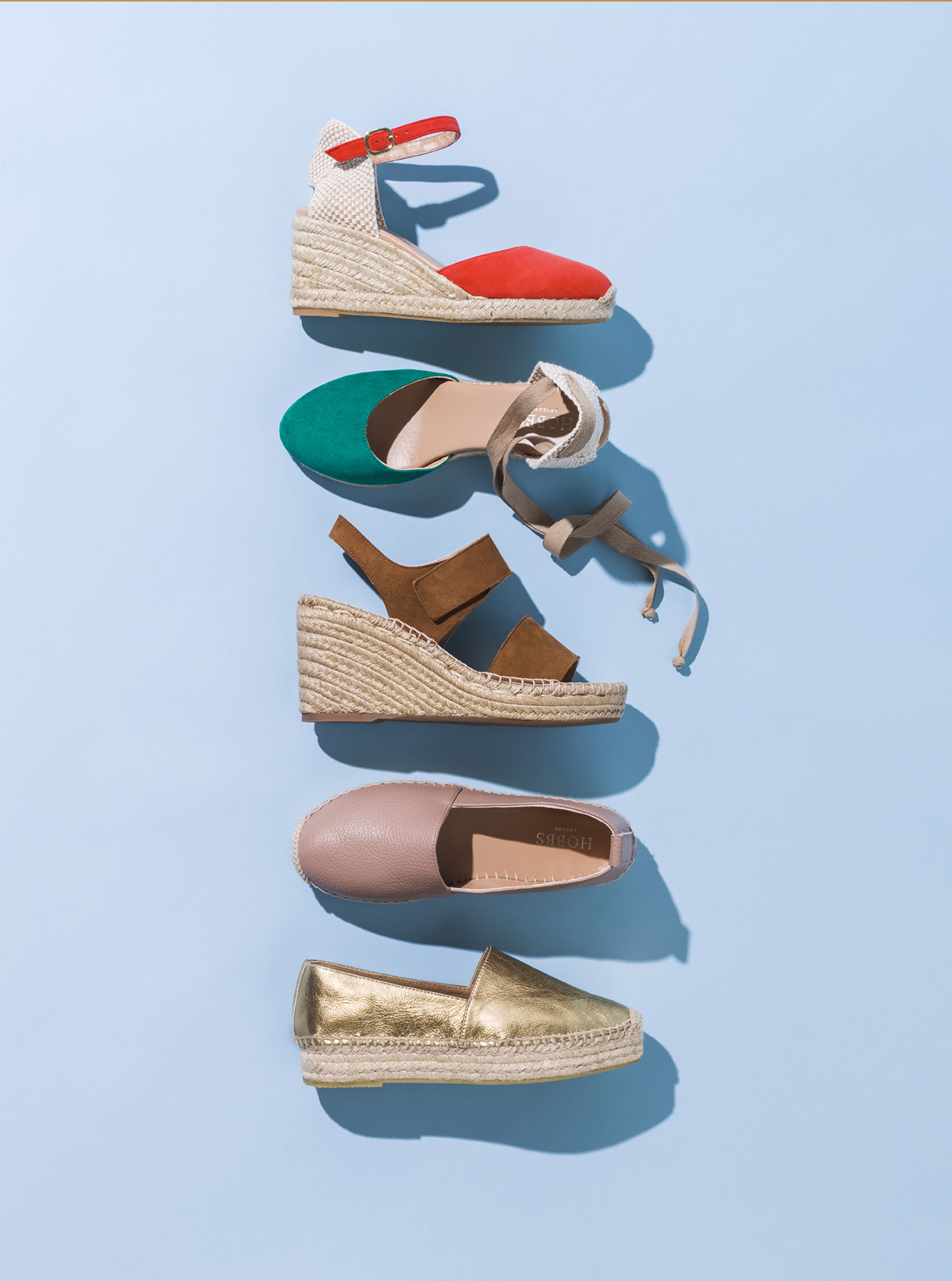 Hobbs espadrille wedges set against a blue background. From top to bottom: Red, green, brown, nude and gold.