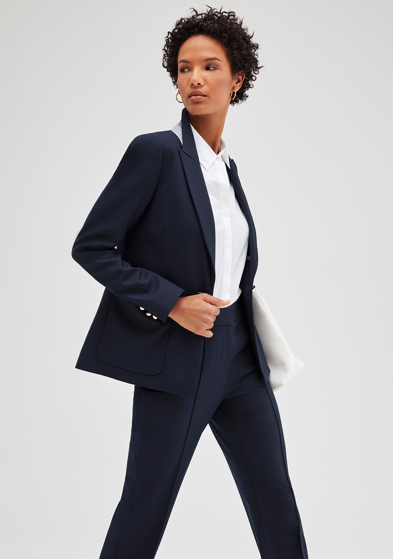Model poses in a classic nevy blue tailored trouser suit styled with a white shirt