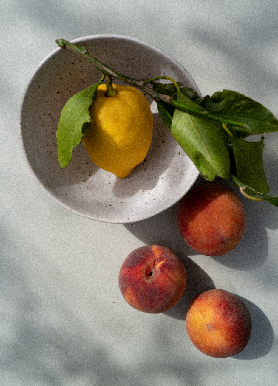 Photograph of a lemon branch in a bowl surrounded by peaches, captured by photographer Charlotte Bland.
