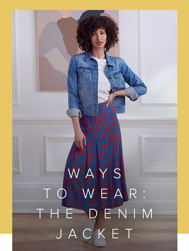 Photographed in front of contemporary abstract art, model wears a denim jacket with a white t-shirt, floral midi skirt and trainers.