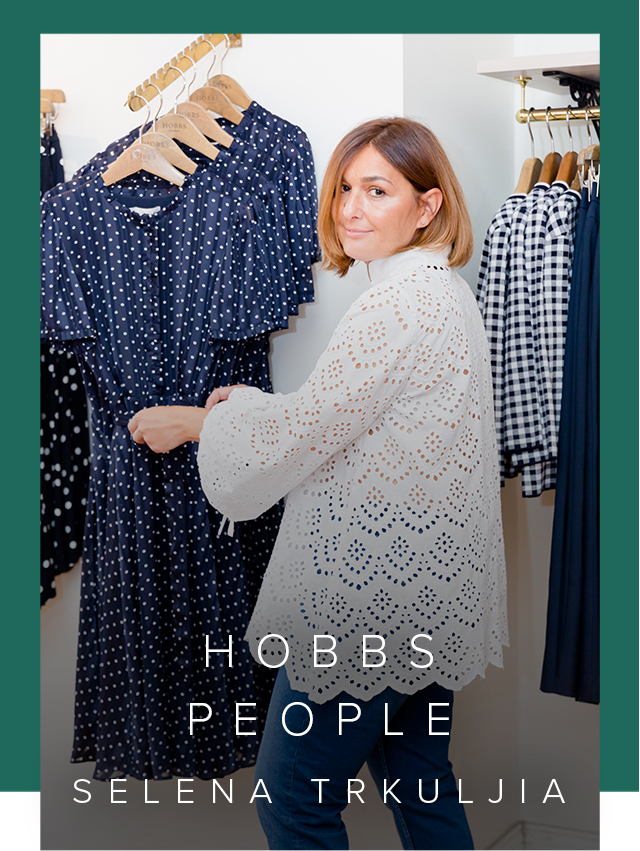 Hobbs UK & International Visual Specialist, Selena Trkuljia, photographed in a Hobbs store wearing a white blouse and blue denim jeans next to several blue dresses hung on a rail.